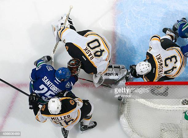 Mike Santorelli of the Vancouver Canucks tries to squeeze the puck through Tuukka Rask, Matt Bartkowski and Kevan Miller of the Boston Bruins during...