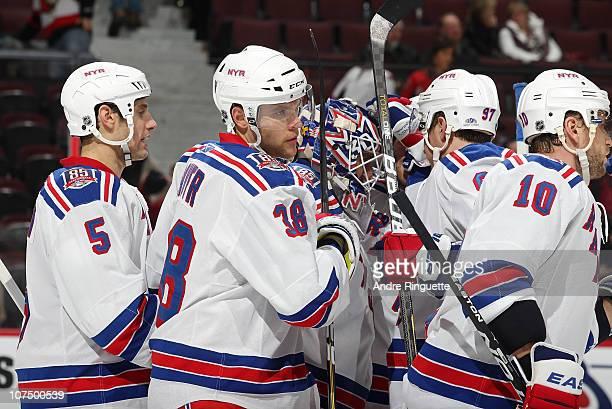 Mike Sauer of the New York Rangers celebrates a win against the Ottawa Senators with teammates Daniel Girardi Henrik Lundqvist and Marian Gaborik at...