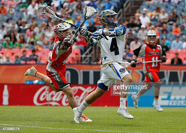 Mike Sawyer of the Charlotte Hounds controls the ball against Domenic Sebastiani of the Colorado Outlaws at Sports Authority Field at Mile High on...