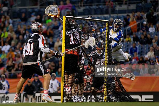 Mike Sawyer of the Charlotte Hounds scores past Jesse Schwartzman of the Denver Outlaws as Dillon Roy and Domenic Sebastiani look on during the...