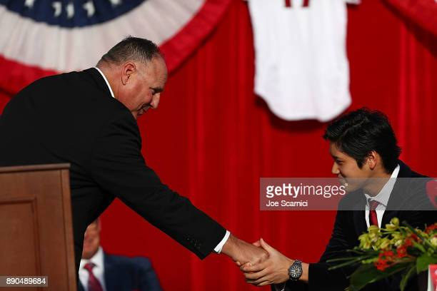 Mike Scioscia and Shohei Ohtani shake hands during the Shohei Ohtani introduction to the Los Angeles Angels of Anaheim at Angel Stadium of Anaheim on...