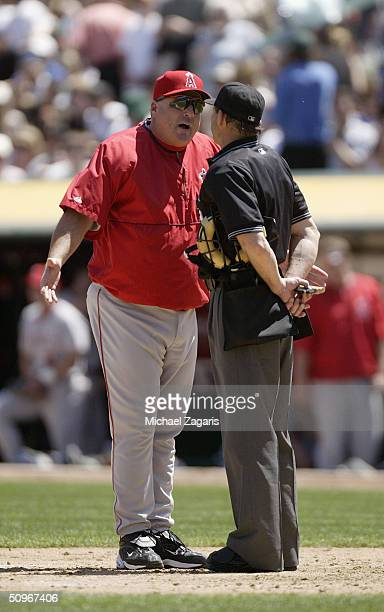 Mike Scioscia of the Anaheim Angels talks to home plate umpire Bill Hohn during the MLB game against the Oakland Athletics at Network Associates...