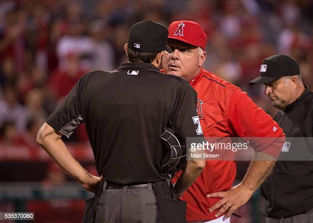 Mike Scioscia of the Los Angeles Angels of Anaheim argues with umpire John Tumpane after starting pitcher Hector Santiago was ejected from the game...