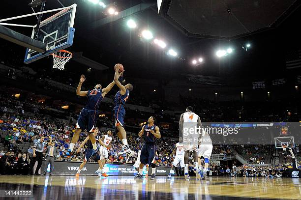 Mike Scott and Akil Mitchell of the Virginia Cavaliers control a rebound in the first half against the Florida Gators during the second round of the...
