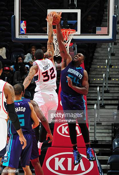 Mike Scott of the Atlanta Hawks has his shot blocked by Jason Maxiell of the Charlotte Hornets on October 20 2014 at Philips Arena in Atlanta Georgia...