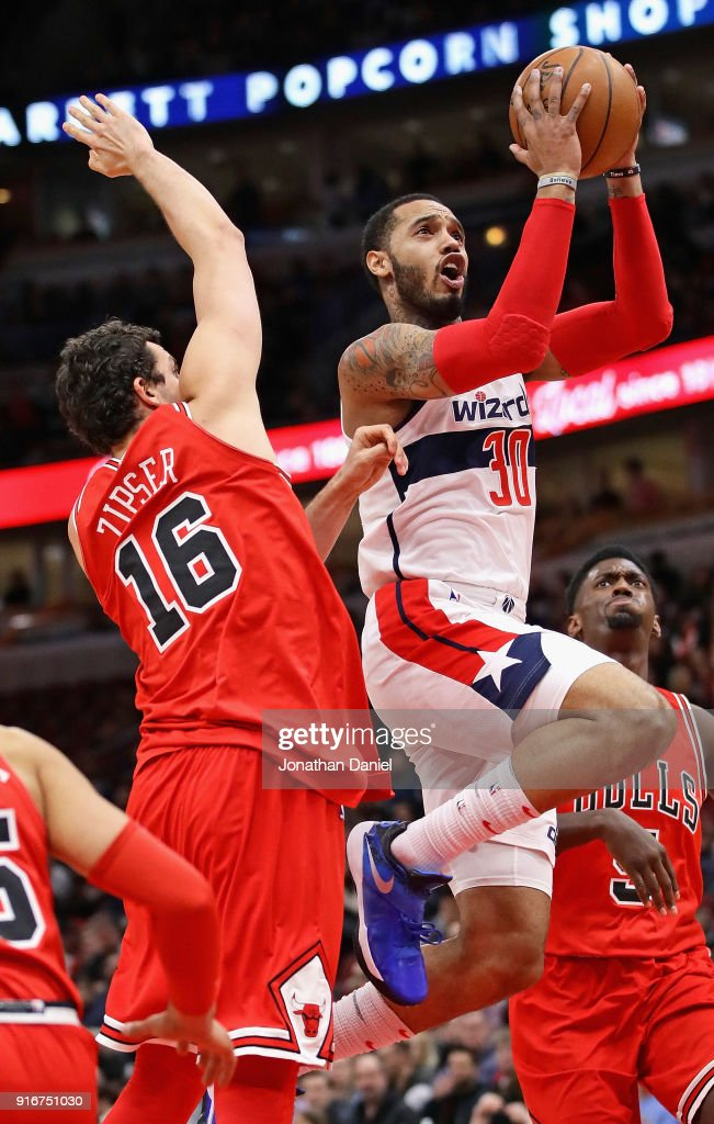 Mike Scott #30 of the Washington Wizards drives between Paul Zipser #16 and Bobby Portis #5 of the Chicago Bulls at the United Center on February 10, 2018 in Chicago, Illinois.