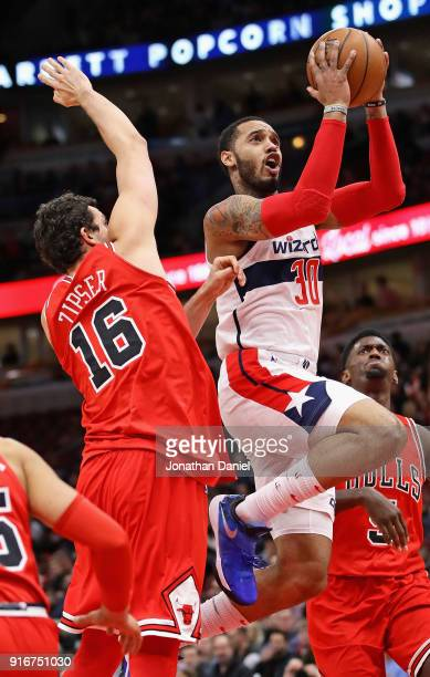 Mike Scott of the Washington Wizards drives between Paul Zipser and Bobby Portis of the Chicago Bulls at the United Center on February 10 2018 in...