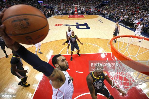 Mike Scott of the Washington Wizards dunks in front of Andre Iguodala of the Golden State Warriors during the first half at Capital One Arena on...