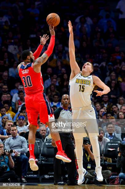 Mike Scott of the Washington Wizards shoots over Nikola Jokic of the Denver Nuggets during an NBA game at the Pepsi Center on October 23 2017 in...