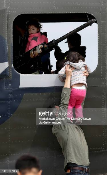 Mike Sherback holds his 2yearold daughter Lily for a view of the Consolidated B24 Liberator Witchcraft on display at the Wings of Freedom Tour at...