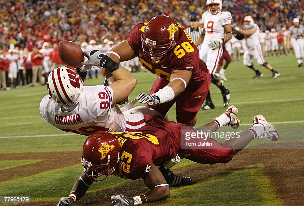 Mike Sherels and Dominique Barber of the Minnesota Golden Gophers break up a pass intended for Garrett Graham of the Wisconsin Badgers the during an...