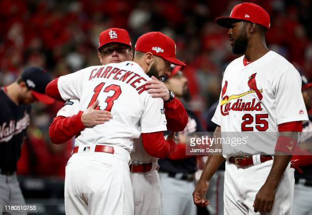 Mike Shildt of the St Louis Cardinals hugs Matt Carpenter as Dexter Fowler looks on prior to game one of the National League Championship Series...