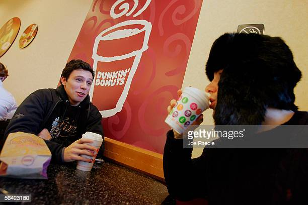 Mike Silverman and Theordore Bressman drink their coffee in a Dunkin' Donuts store December 12, 2005 in Cambridge, Massachusetts. According to...