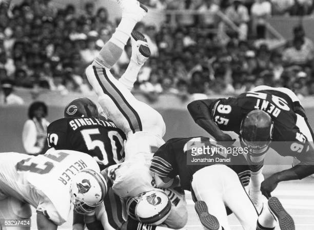 Mike Singletary and Gary Fencik of the Chicago Bears tackle James Wilder of the Tampa Bay Buccaneers during the game at Soldier Field on September 8,...