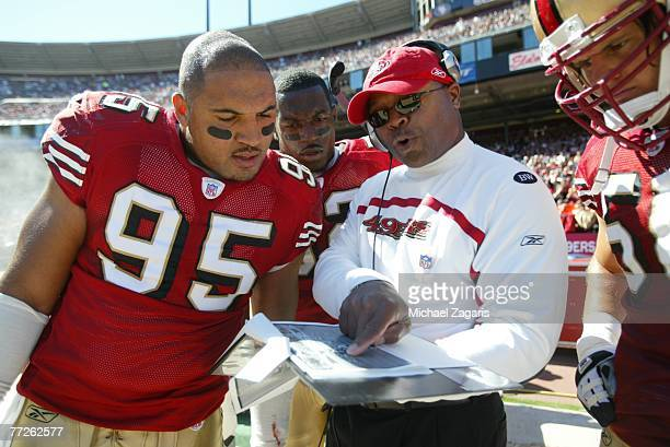 Mike Singletary meets with Tully BantaCain Patrick Willis and Derek Smith of the San Francisco 49ers during the NFL game against the Baltimore Ravens...