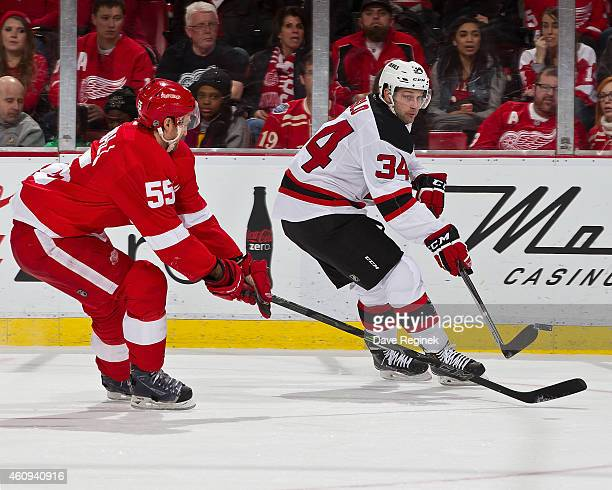 Mike Sislo of the New Jersey Devils takes a back hand shot as Niklas Kronwall of the Detroit Red Wings defends during the annual New Year's eve game...