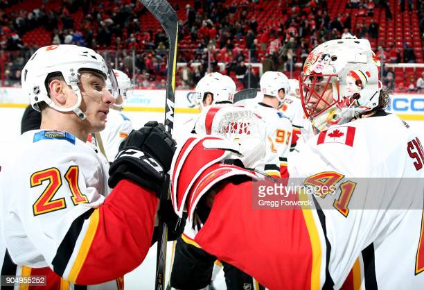 Mike Smith and Garnet Hathaway of the Calgary Flames celebrate their 41 victory over the Carolina Hurricanes following an NHL game on January 14 2018...