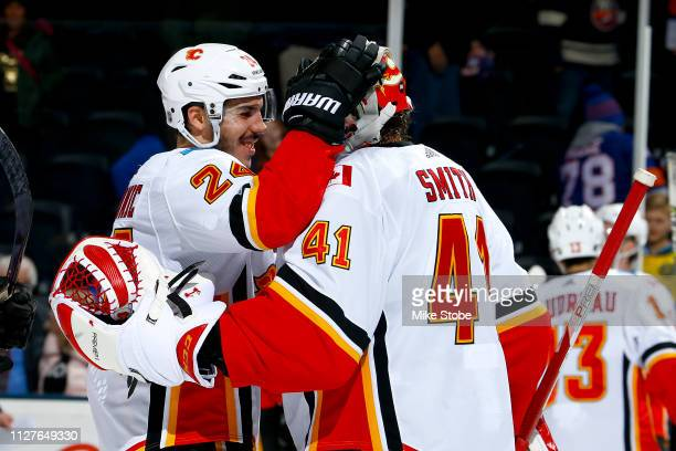 Mike Smith and Travis Hamonic of the Calgary Flames celebrate their teams 3-1 win over the New York Islanders at NYCB Live's Nassau Coliseum on...