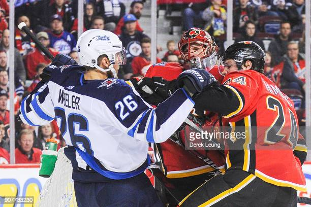 Mike Smith and Travis Hamonic of the Calgary Flames shove Blake Wheeler of the Winnipeg Jets during an NHL game at Scotiabank Saddledome on January...