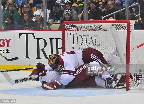 Mike Smith falls down in front of the net after being run into by one of his players of the Arizona Coyotes against the Pittsburgh Penguins at Consol...