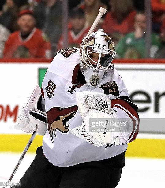 Mike Smith of the Arizona Coyotes knocks the puck away with his glove against the Chicago Blackhawks at the United Center on December 6 2016 in...