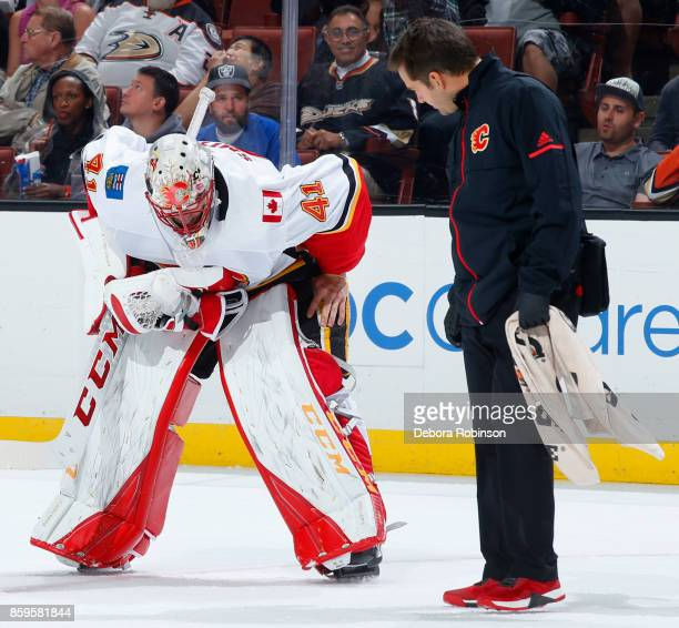 Mike Smith of the Calgary Flames gets attention from the trainer after a whistle during the game against the Anaheim Ducks on October 9 2017 at Honda...