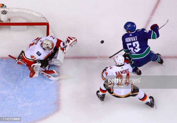 Mike Smith of the Calgary Flames looks on as Travis Hamonic of the Calgary Flames checks Bo Horvat of the Vancouver Canucks during their NHL game at...