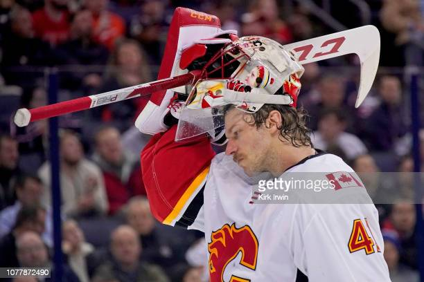 Mike Smith of the Calgary Flames puts on his mask during a stoppage in play in the game against the Columbus Blue Jackets on December 4, 2018 at...