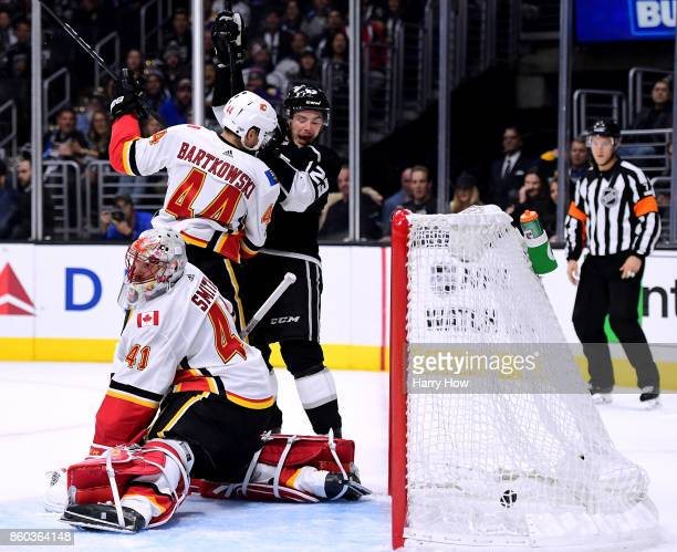 Mike Smith of the Calgary Flames reacts to a goal from Anze Kopitar of the Los Angeles Kings along with Dustin Brown of the Los Angeles Kings and...