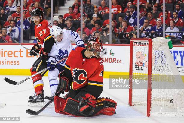 Mike Smith of the Calgary Flames watches the shot of Nikita Zaitsev of the Toronto Maple Leafs fly past him during an NHL game at Scotiabank...