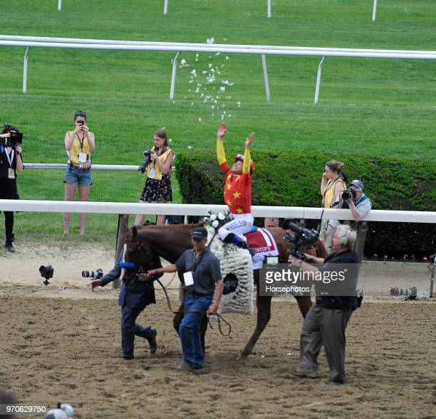 Mike Smith spreads flowers after Justify with Mike Smith up wins the Belmont Stakes and Triple Crown at Belmont Park Racetrack on June 09 2018 in...