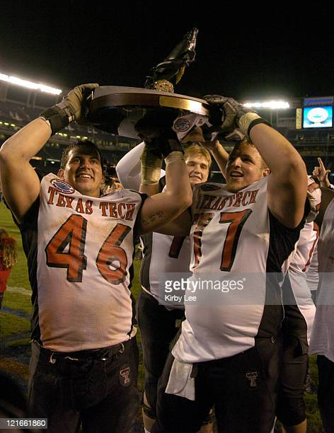 Mike Smitih and Dylan Gandy of Texas Tech hoist championship trophy after 4531 victory over Cal in the Pacific Life Holiday Bowl at Qualcomm Stadium...