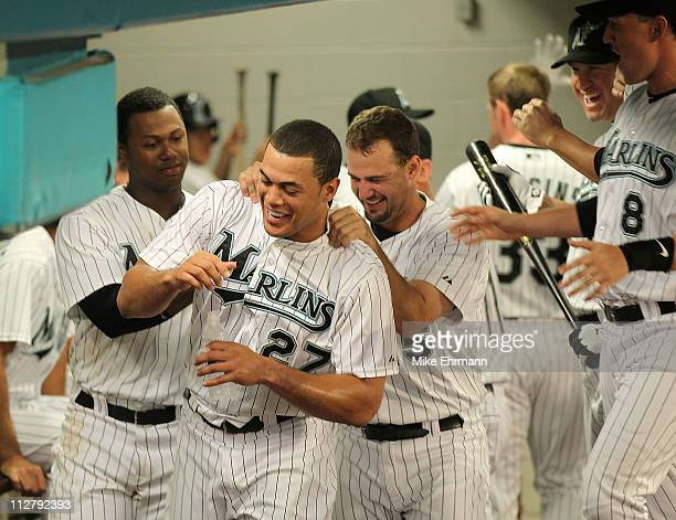 Mike Stanton of the Florida Marlins is congratulated by Hanley Ramirez and Gaby Sanchez after hitting his first home run of the year during a game...