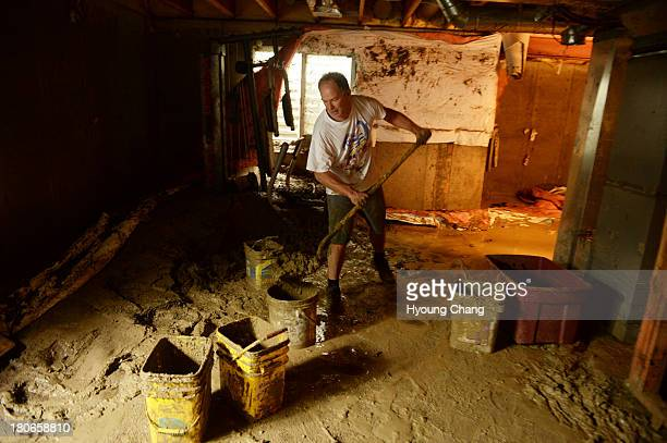Mike Steinpach is moving the mud out from the basement of Stan McDonald's house damaged by flooding near the corner of Widgeon Dr and Allen Drive...
