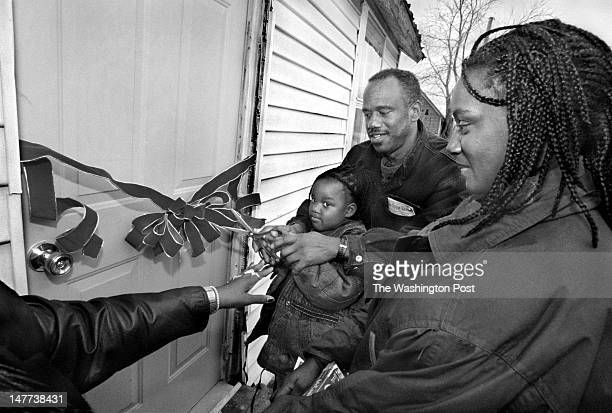 FILE Mike Stewart helps Kadijah Cummings and her mother Victoria Cummings cut the ribbon as they christen their newly refurbished home in Bayview...