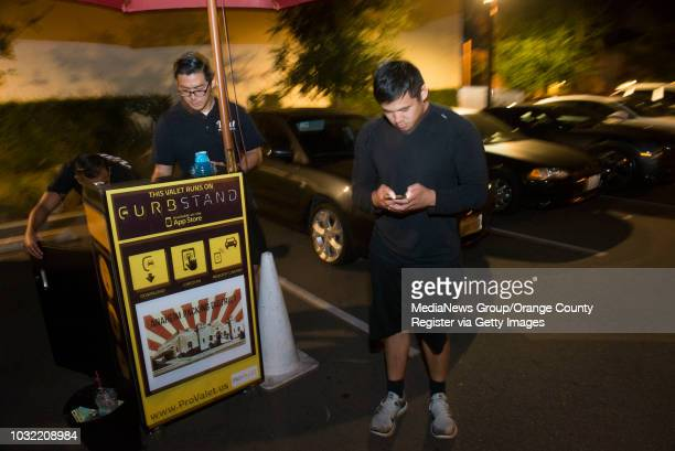 Mike Tabajonda of Long Beach uses the Curbstand App for the first time after having no cash for valet John Park of Chino Hills a the Anaheim Packing...