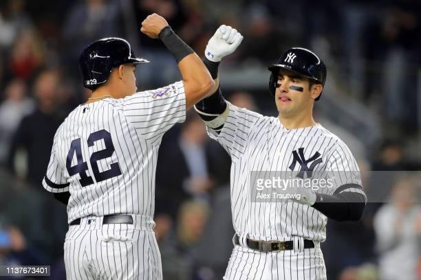 Mike Tauchman of New York Yankees is greeted by teammate Gio Urshela after hitting a tworun home run in the sixth inning during the game between the...