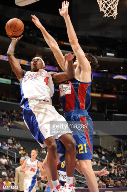 Mike Taylor of the Los Angeles Clippers attempts a shot while avoiding contact from Ersan Ilyasova of Regal FC Barcelona at Staples Center on October...