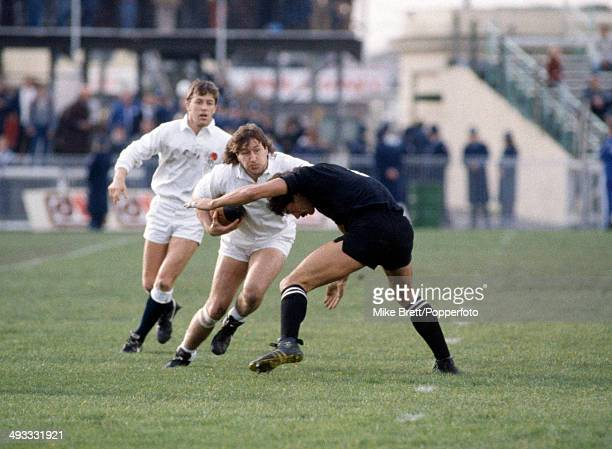 Mike Teague of England is challenged by Murray Mexted of New Zealand with Nigel Melville of England in the background during the First Test match...