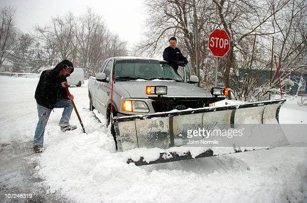 Mike Thauer attempts to dig out plow operator Jon Powers after a five mile wide band of lakeeffect snow dumped more than two feet of snow and closed...