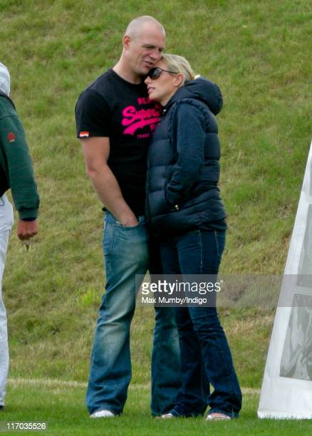 Mike Tindall and Zara Phillips embrace as they watch Prince Harry compete in the Bernard Weatherill Cup charity polo match at Beaufort Polo Club on...