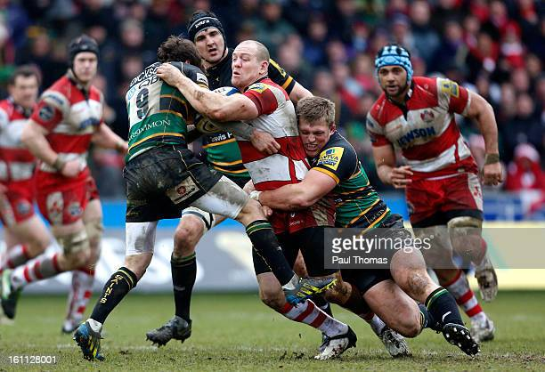 Mike Tindall of Gloucester is tackled by Alex Waller and Lee Dickson of Northampton during the Aviva Premiership match between Northampton Saints and...