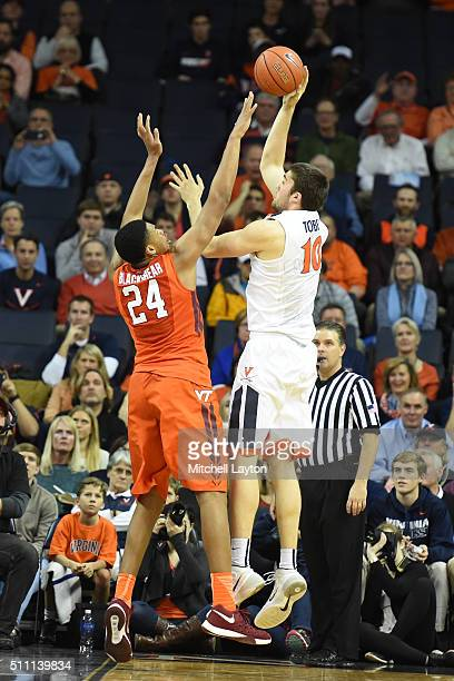 Mike Tobey of the Virginia Cavaliers takes a shot over Kerry Blackshear Jr #24 of the Virginia Tech Hokies during a college basketball game at John...
