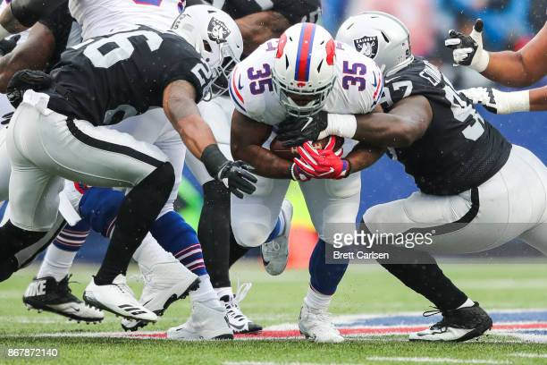 Mike Tolbert of the Buffalo Bills runs the ball as Shalom Luani of the Oakland Raiders and Mario Edwards of the Oakland Raiders attempt to tackle him...