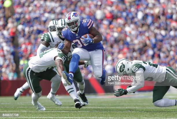 Mike Tolbert of the Buffalo Bills runs with the ball during NFL game action as he breaks a tackle from Julian Stanford of the New York Jets and...