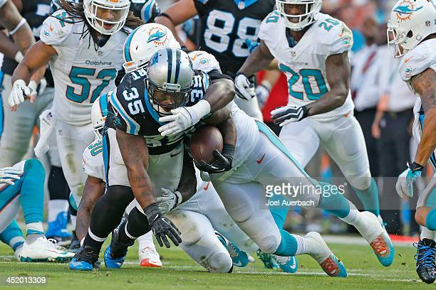 Mike Tolbert of the Carolina Panthers is tackled by Dannell Ellerbe of the Miami Dolphins on November 24 2013 at Sun Life Stadium in Miami Gardens...