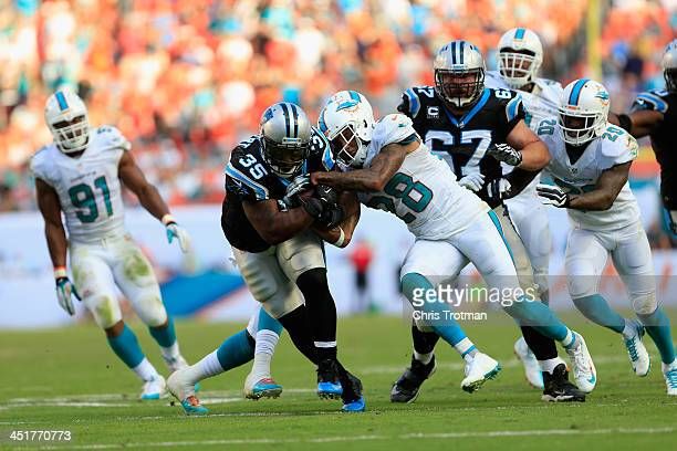 Mike Tolbert of the Carolina Panthers is tackled by Nolan Carroll of the Miami Dolphins at Sun Life Stadium on November 24 2013 in Miami Gardens...