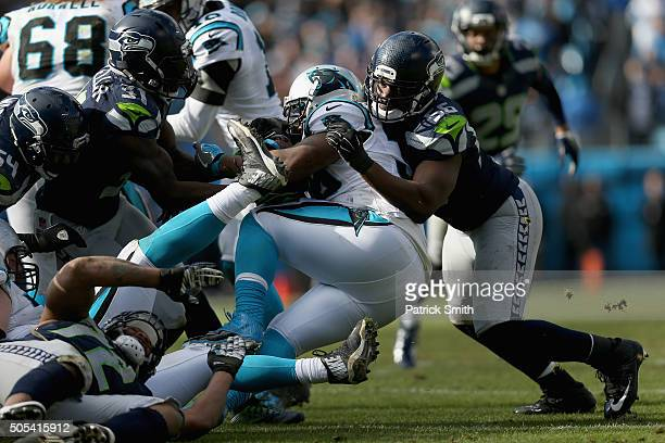 Mike Tolbert of the Carolina Panthers runs the ball against Cliff Avril of the Seattle Seahawks in the 3rd quarter during the NFC Divisional Playoff...