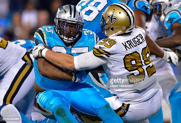 Mike Tolbert of the Carolina Panthers runs the ball against Paul Kruger of the New Orleans Saints in the 4th quarter during the game at Bank of...