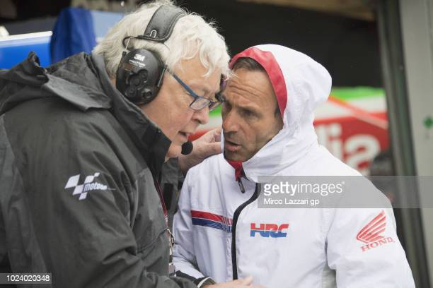 Mike Trimby of Great Britain and President of Irta speaks with Alberto Puig of Spain in box waiting the start of the MotoGP race during the MotoGp Of...